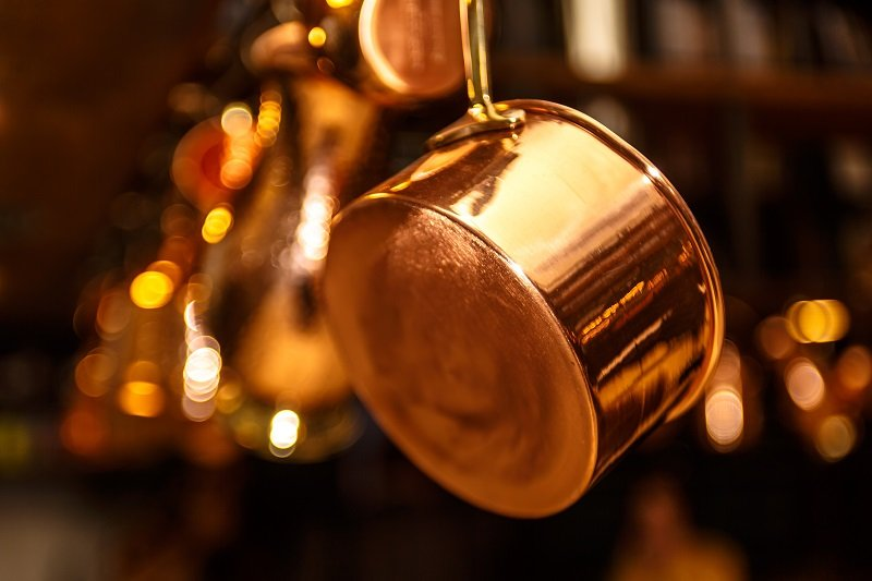 Copper kitchenware (pots, pans, jugs) hang from the ceiling in the kitchen.