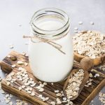 Oat flakes milk in glass jar on stone table. Vegan non dairy alternative milk.