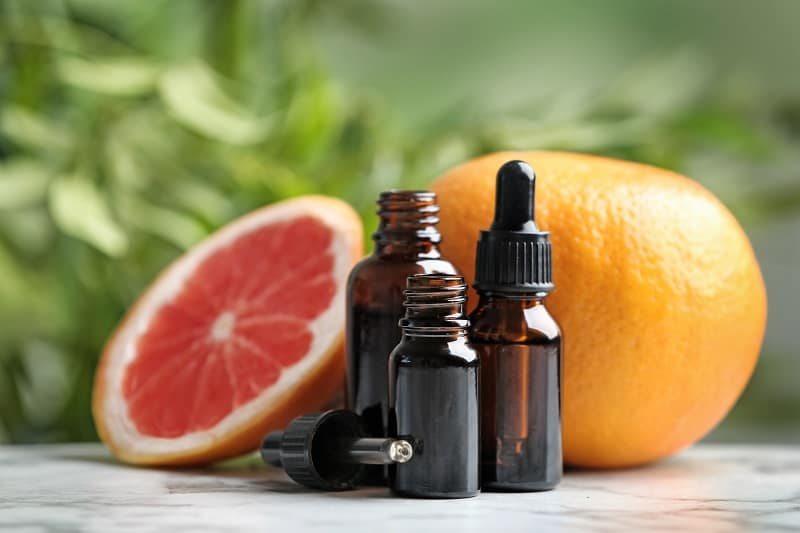 Bottles of essential oil and grapefruit on table against blurred background