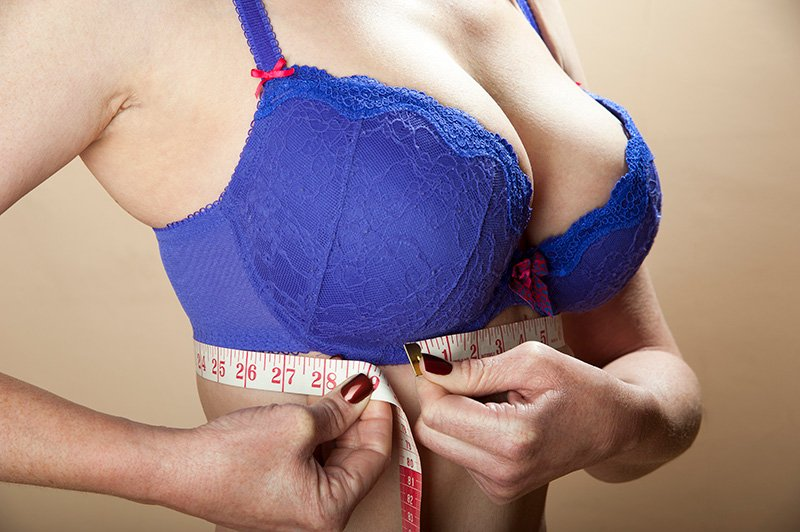 Woman using a tape measure to check rib cage size