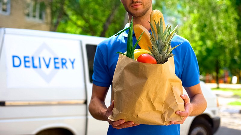 Male worker holding grocery bag delivering food to home