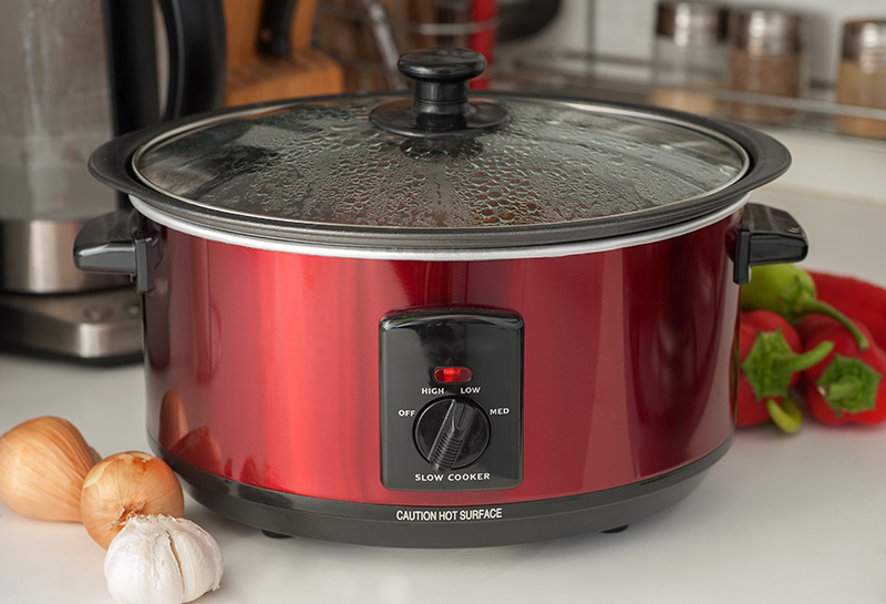 Red slow cooker on table with vegetables
