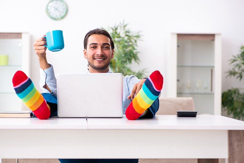 Man enjoying working from home sitting with his feet up and holding a cup of coffee in his hand