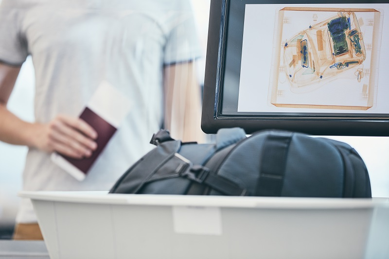 Airport security check. Young man holding passport and waiting for x-ray control his luggage.