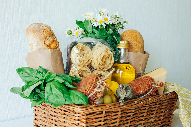 Artisanal food gift basket with bread, basil, pasta, olives and olive oil
