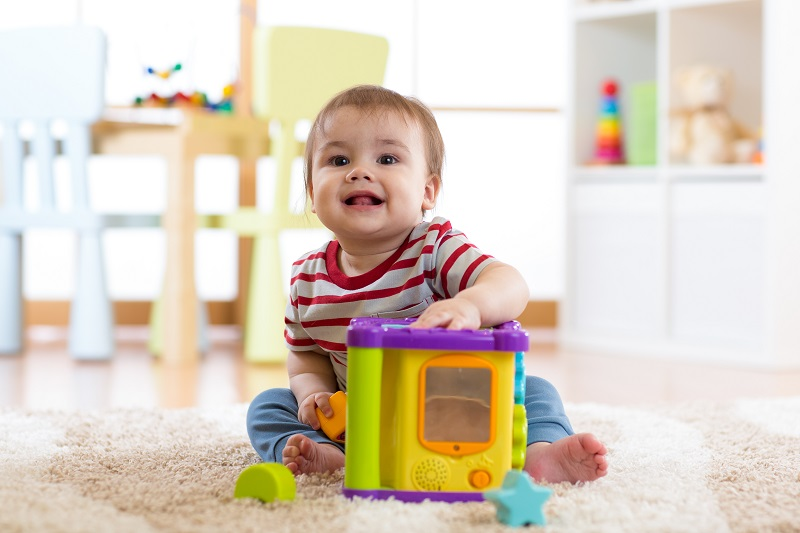 toddler baby boy playing indoors with sorter toy sitting on soft carpet