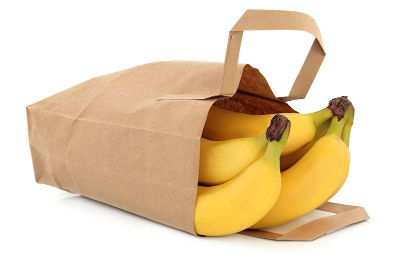 Stem of bananas in brown paper bag