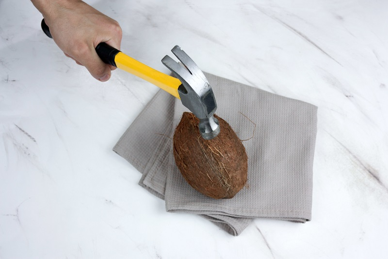 man;s hand with hammer and coconut on a marble background top view