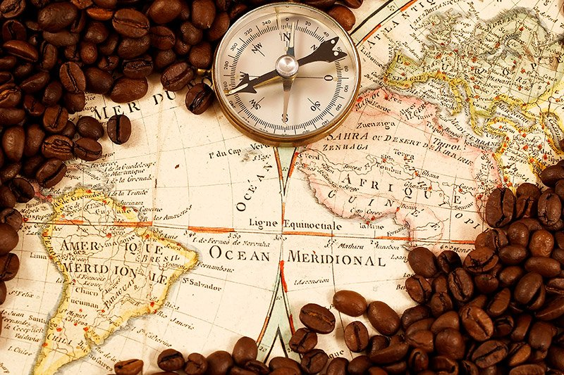 Coffee beans and compass on world map