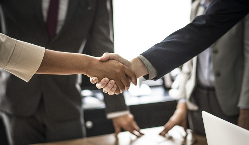 woman and man in business suits shake hands
