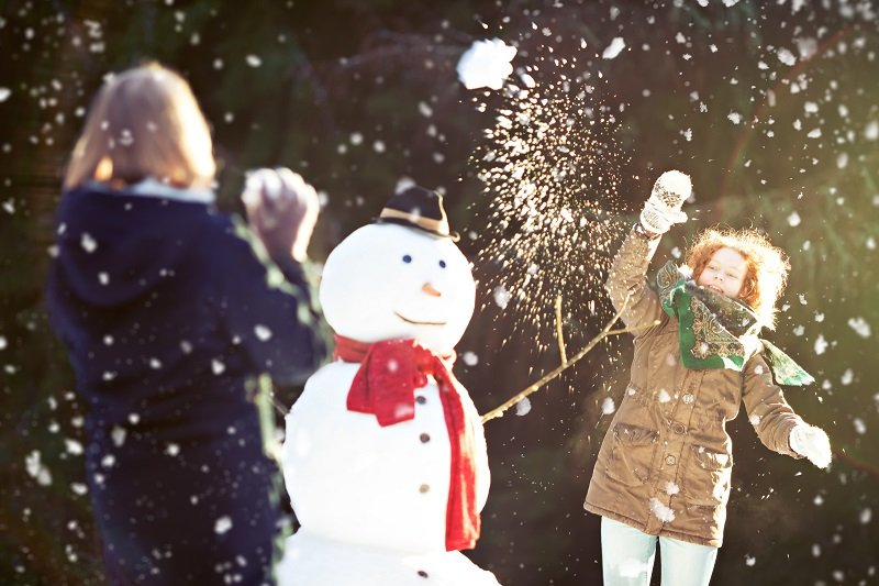 snowman and two girls having a snowball fight