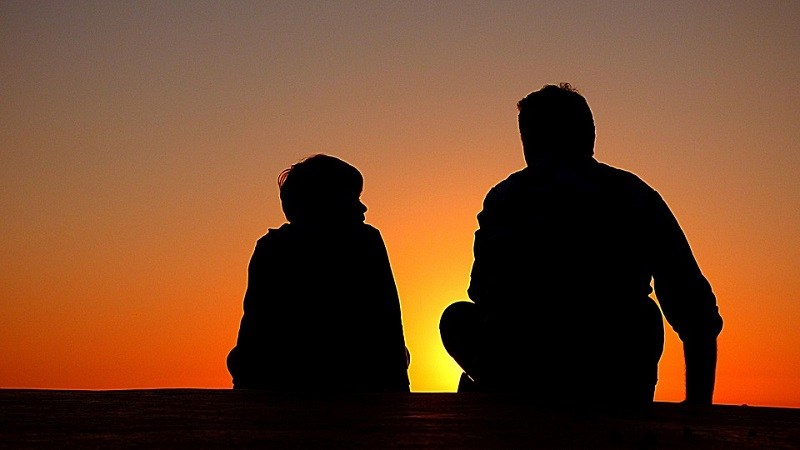 man and boy silhouette sunset