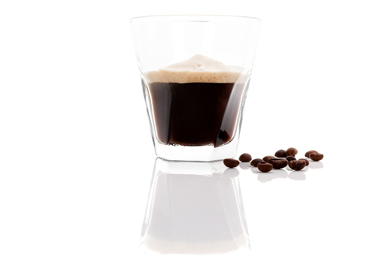 Espresso shot with coffee beans on white background