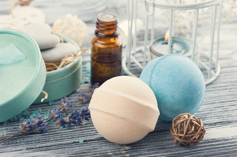SPA composition with bath bombs, essential oil, lavender flowers, lit candles. Wooden background