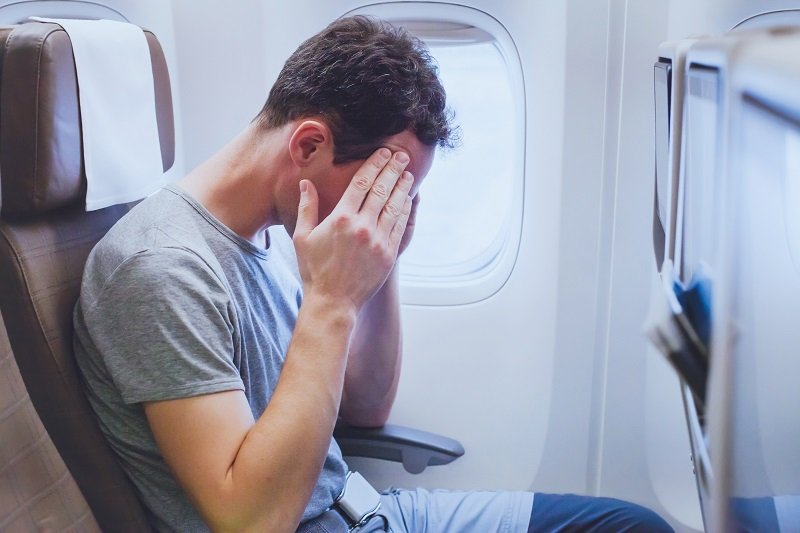man in airplane, man passenger afraid and feeling bad during the flight in plane