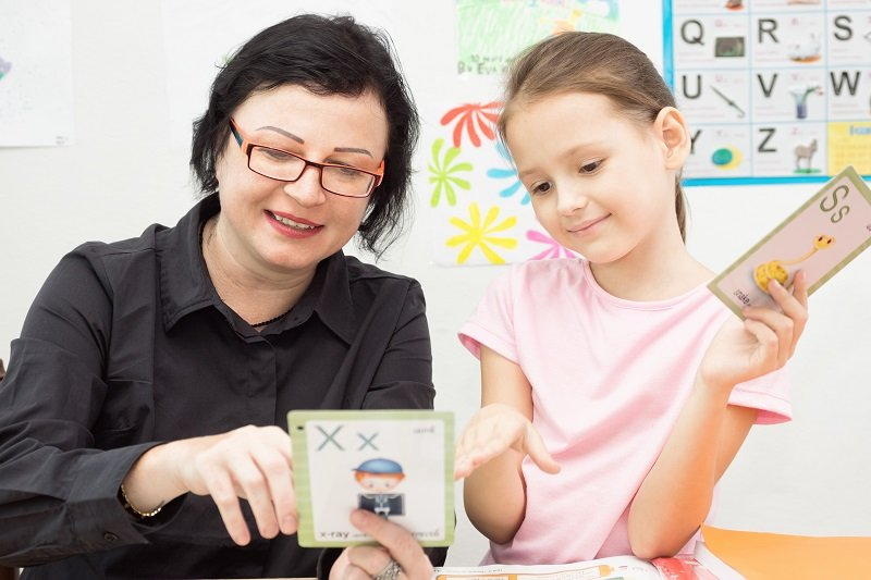 Woman teacher and school girl study with flash cards. Classroom in background. Education game concept