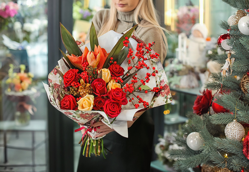 Female florist holding beautiful Christmas bouquet in flower shop