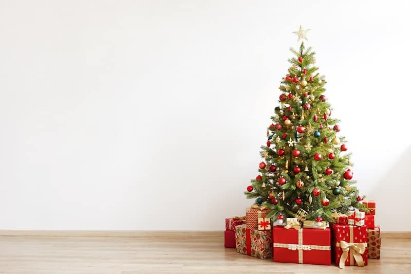 Big beautiful christmas tree decorated with beautiful shiny baubles and many different presents on wooden floor. White wall background with a lot of copy space for text. Close up.