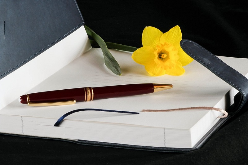 journal with flower and pen