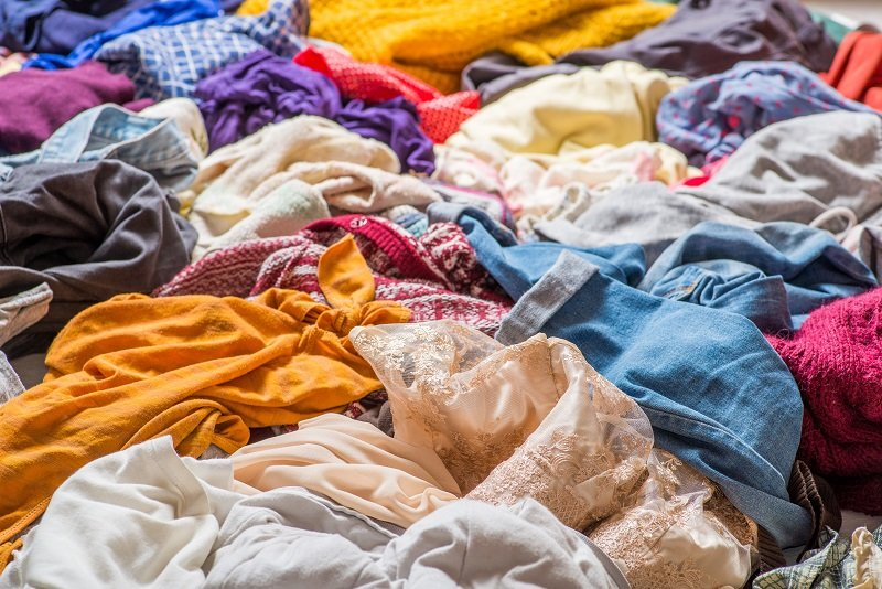 pile of used clothes on a light background. Second hand for recycling