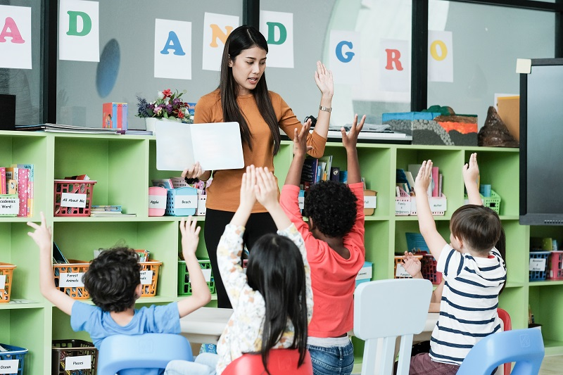 Young asian woman teacher teaching kids in kindergarten classroom, preschool education concept