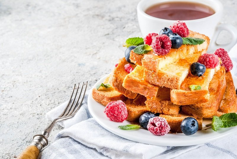 Healthy summer breakfast, baked french toasted bread sticks with fresh berry and honey, morning light grey stone background copy space