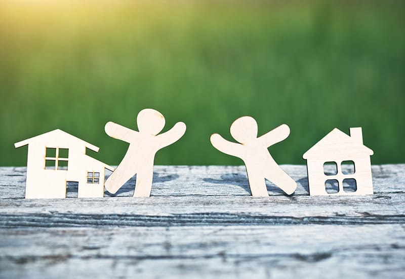 Illustration of little wooden men in houses symbolizing neighborhood, friendship and teamwork
