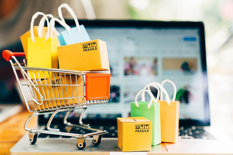 Online shopping illustrated with cart full of goods on top of laptop