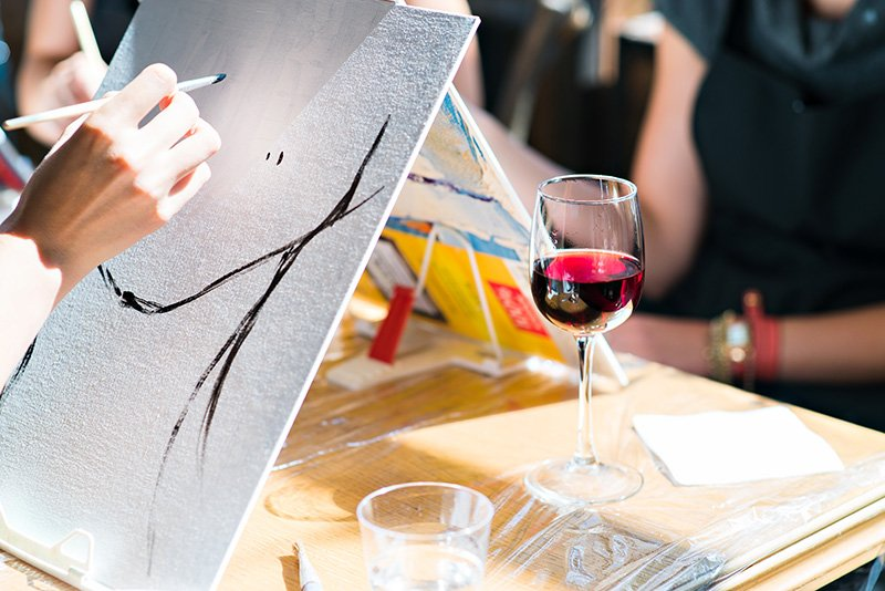 Women painting and drinking wine