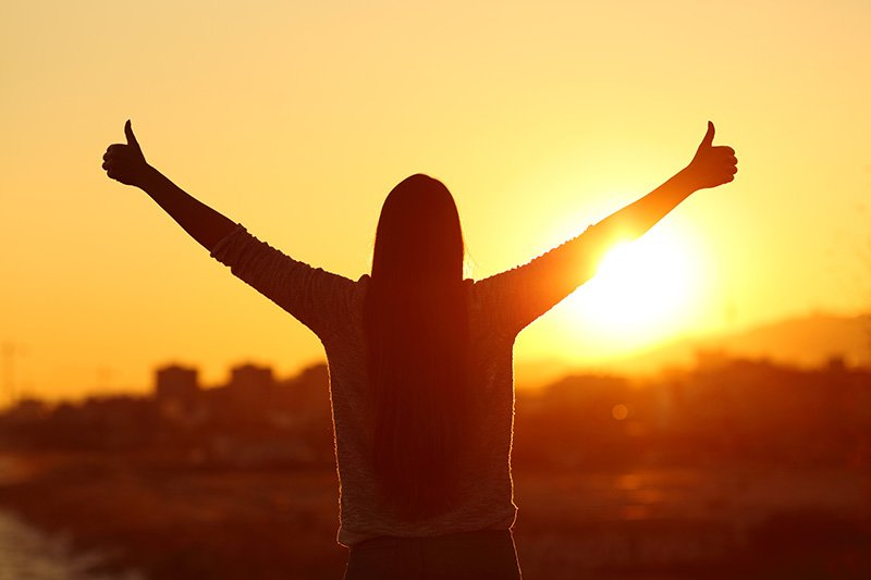Backlight of a woman raising arms with thumbs up