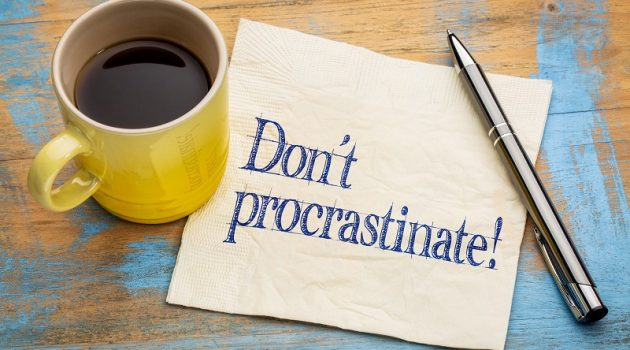 do not procrastinate reminder - handwriting on a napkin with a cup of coffee