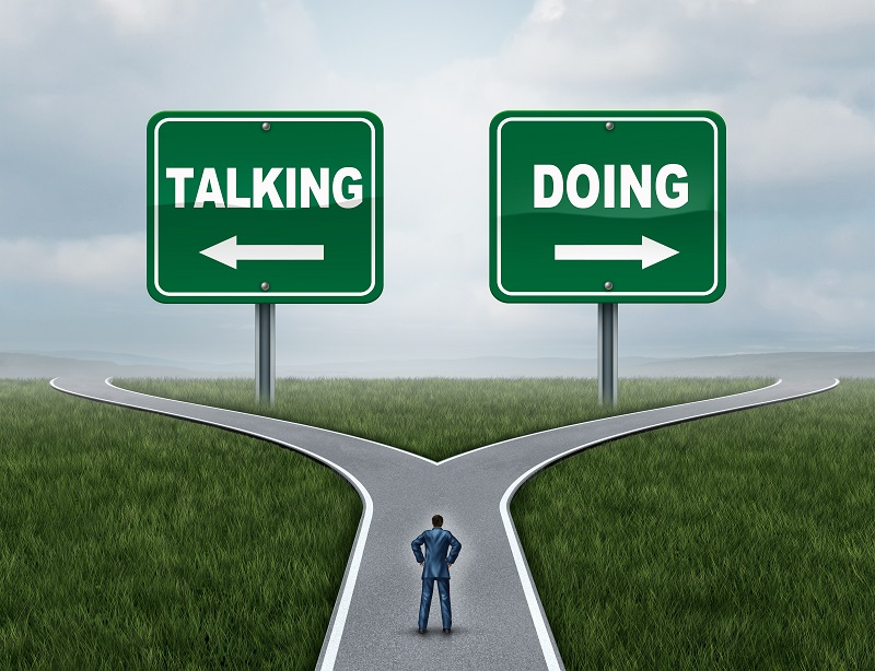Motivation concept as a courage and fear metaphor with a person at a crossroad with talking or doing signs for talkers versus doers