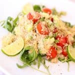 quinoa served with lemon slices and tomatoes on a bed of salad greens