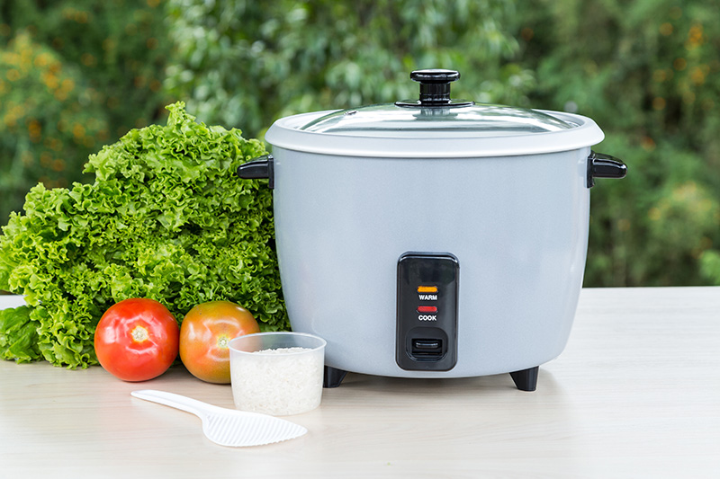 Rice cooker and vegetables on table