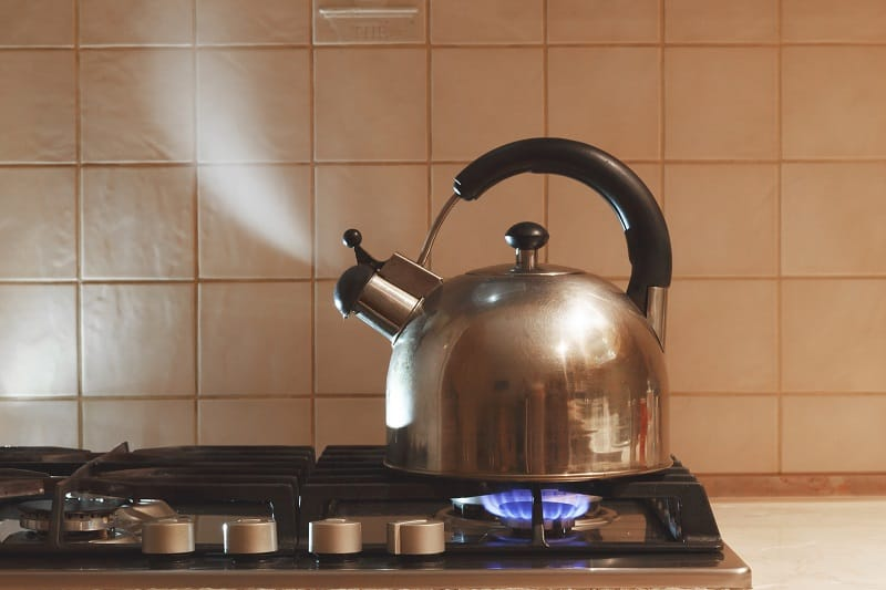 Water boils in a metal teapot on a gas stove.
