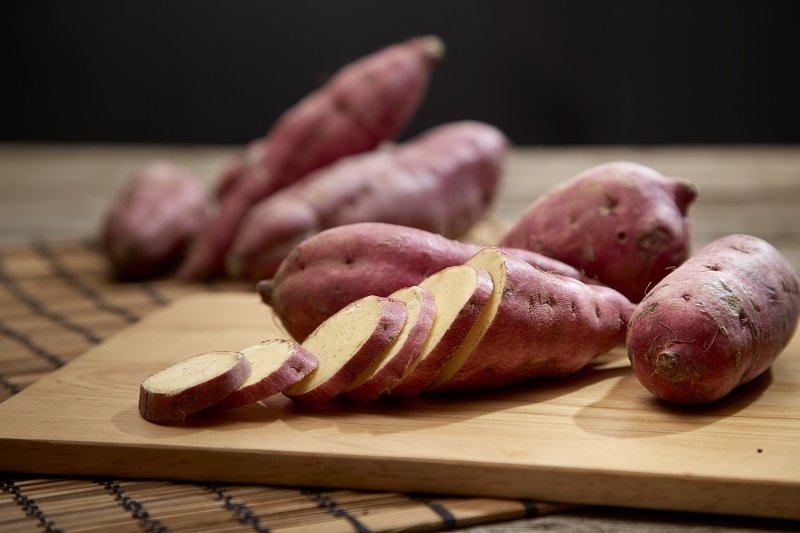 Raw purple sweet potato on rustic wooden table in kitchen