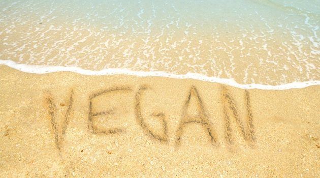 Vegan written in the sand on a tropical beach for a vegan vacation concept