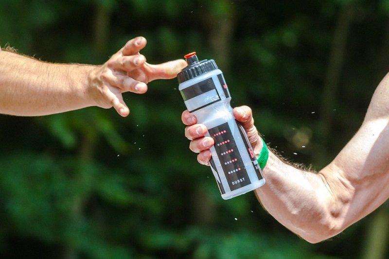 person passes water bottle to another