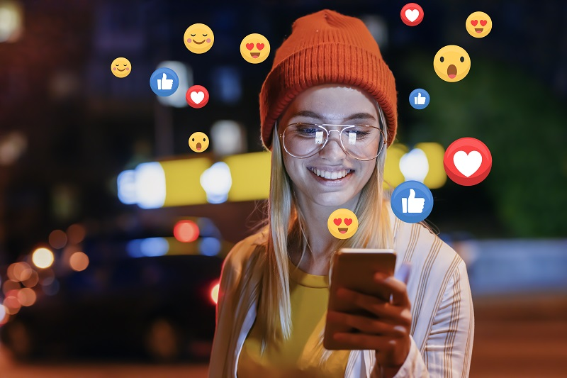 girl with Smartphone getting heart emojies, likes, and followers on social media