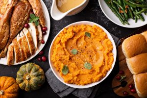 Mashed sweet potatoes with butter and cinnamon on Thanksgiving table with turkey and green beans overhead shot