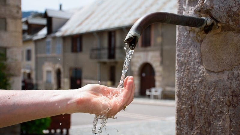 hand under water pipe cool drinking water