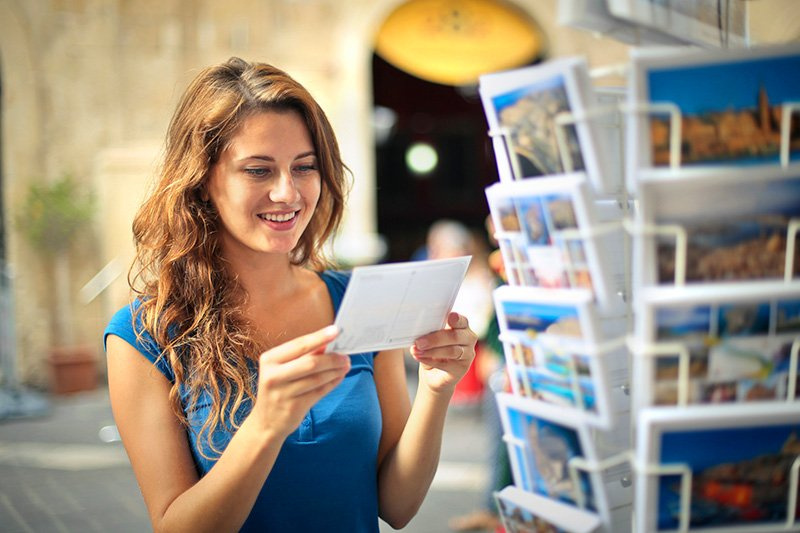 Smiling woman choosing a postcard