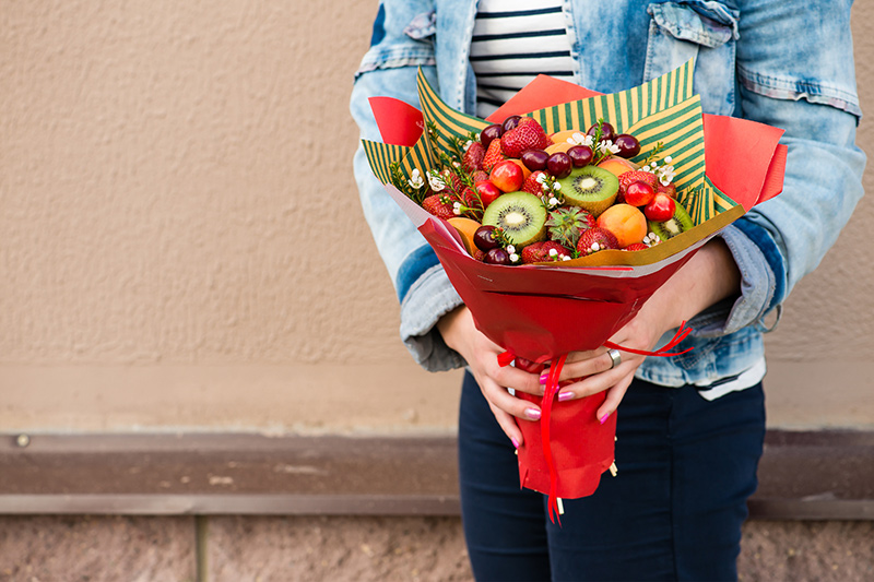 Woman holding fruit bouquet