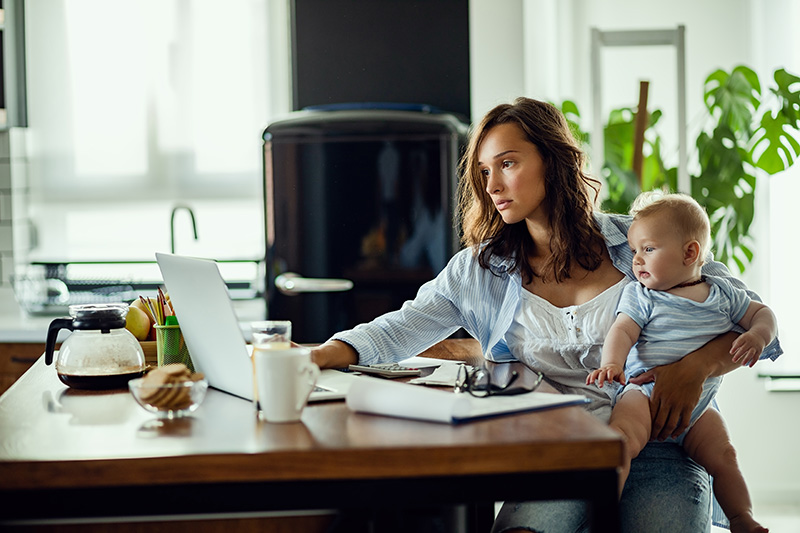 Woman trying to work from home but she seems tired of being interrupted by her child